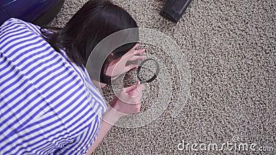 Młoda kobieta bada dywan ze szkła powiększającego, widok z góry zbiory wideo