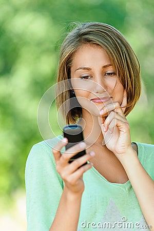 Młoda kobieta czyta sms na wiszącej ozdobie
