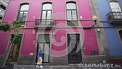 Młoda kobieta dobrze się bawi i przechodzi obok pięknego różowego budynku w kolorowym hiszpańskim mieście Szeroki kąt Przygoda zbiory