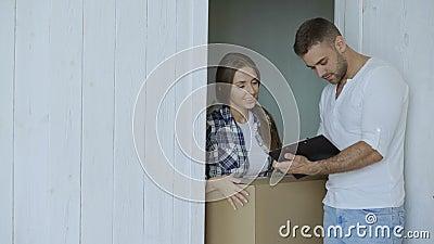 Młoda kobieta dostarcza karton klient w domu Mężczyzna podpisuje wewnątrz schowek dla odbiorczego pakuneczka zdjęcie wideo