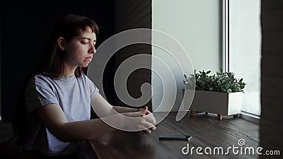 Młoda kobieta napoju kawa przy kawiarnią, robi łyczkowi i patrzeje okno zbiory