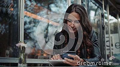Młoda kobieta trzyma kredytową kartę i używa laptop Online zakupy pojęcie w nowożytnej cukiernianej szczęśliwej brunetki dziewczy