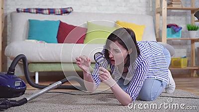 Młoda kobieta w salonie przez lupę bada dywan zdjęcie wideo