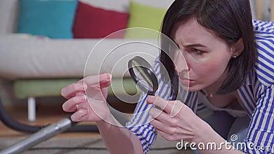 Młoda kobieta w salonie przez szkło powiększające bada dywan w pobliżu zbiory