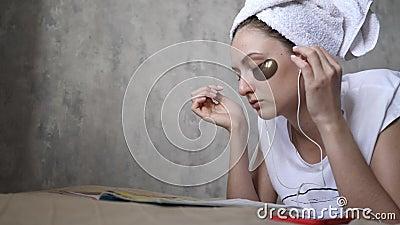 Młoda kobieta wkłada słuchawki i cieszy się muzyką w dzień wolny Kosmetyki, ranek, relaks zdjęcie wideo