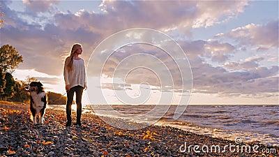 Młoda kobieta z psią pozycją obok brzeg jezioro lub morze Przy zmierzchem, patrzejący w odległość, marzy zbiory wideo