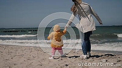 Młoda matka i mała córka w żółtej kurtce spacerują po morskiej plaży zdjęcie wideo