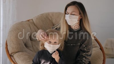 Młoda Matka W Masce Medycznej Nakłada Maskę Na Swoją Córkę, Ale Dziewczynka Wychodzi zdjęcie wideo