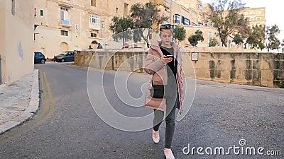 Młoda nastoletnia dziewczyna w różowej kurtce chodzi z gadką i telefonem Kamienne ściany, turysta, ogólnospołeczne sieci, atrakcy zbiory wideo