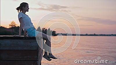 Młoda Nikła dama jest above Siedzącym - wodą przy lato zmierzchu Relaksować i łuną zbiory wideo
