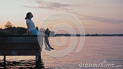 Młoda Nikła kobieta jest above Siedzącym - wodą przy lato zmierzchu Relaksować i łuną zdjęcie wideo