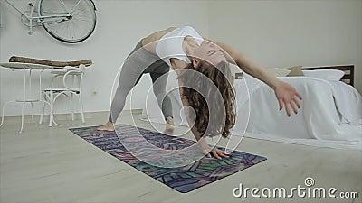 Młoda sportowiec ćwiczy jogę podczas skomplikowanych ćwiczeń w domu Zbliżenie Widok z boku Kamera przesuwa się do tyłu i zbiory wideo