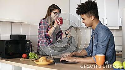 Młoda szczęśliwa para modnisie siedzi w kuchni, oba używa niektóre przyrząda lubi laptop, smartphone, no opowiada zbiory