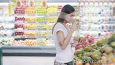 Młoda turystka wybiera owoce mango w supermarkecie, węszy i zabiera je zbiory wideo