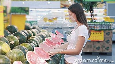 Młoda turystka wybiera połowę arbuza w supermarkecie, wąchuje, bierze zbiory wideo