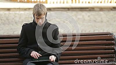 Młodego człowieka obsiadanie i pisać na maszynie na pastylce zbiory