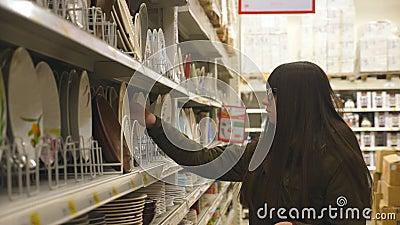 Młodej dziewczyny kupienia talerze w sekci dishware Piękna kobieta bierze few talerze i stawia one w koszu femaleness zbiory wideo