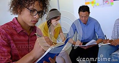 Młodej rasy męski kierownictwo pisze na dzienniczku w nowożytnym biurze 4k zbiory