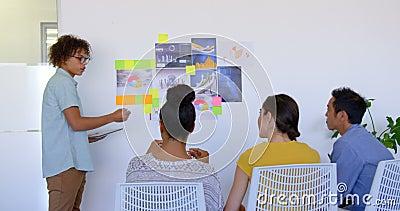Młodej rasy męski kierownictwo wyjaśnia o wykresach i kleistych notatkach w nowożytnym biurze 4k zdjęcie wideo