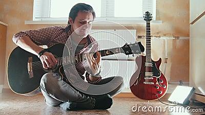 Młody atrakcyjny muzyk bawić się gitary obsiadanie na podłoga w kuchni zbiory