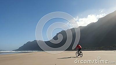 Młody człowiek jedzie bicykl na piasek plaży na wyspach kanaryjskich w pięknym wschód słońca świetle przeciw fantastycznym górom  zdjęcie wideo