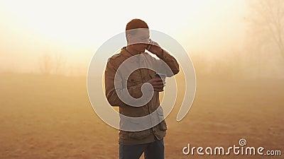 Młody człowiek pije jego ranek kawę i ślimacznica telefon komórkowego z zadziwiającym widokiem w żakiecie i używa podczas wschód  zbiory wideo