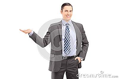 Młody fachowy mężczyzna gestykuluje z jego ręką w kostiumu