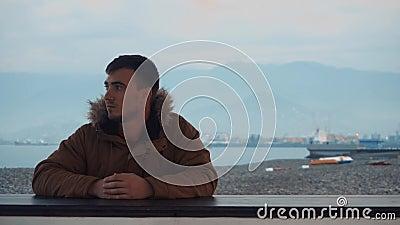 Młody mężczyzna patrzy na tle gór, wybrzeża morskiego, łodzi, pięknego krajobrazu zbiory