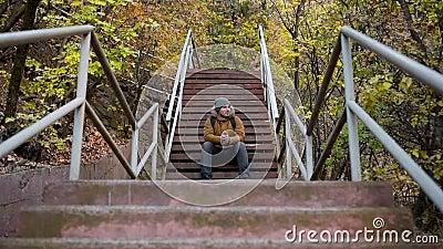Młody mężczyzna siedzi na schodach w naturze Symetria Symetryczna ramka kinowa zdjęcie wideo