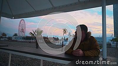 Młody mężczyzna stoi w pustym i opuszczonym miejscu, na tle koła Ferrisa, w różnych budynkach A zdjęcie wideo