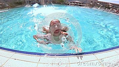 Młody nikły kobiety doskakiwanie w basen i dopłynięcie pod wodą zbiory
