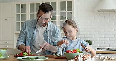 Młody ojciec uczy córkę kroić sałatkę warzywną w kuchni zbiory wideo