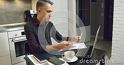 Młody przedsiębiorca, który rozmawia z klientami lub partnerami na temat umowy lub raportu za pomocą słuchawek i laptopów zbiory