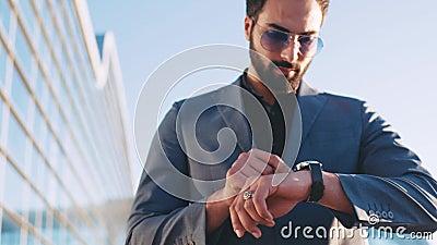 Młody przystojny mężczyzna w kostiumu omijaniu lotniskowym terminal i używać mądrze zegarek Nowożytni przyrząda, ruchliwie styl ż zbiory