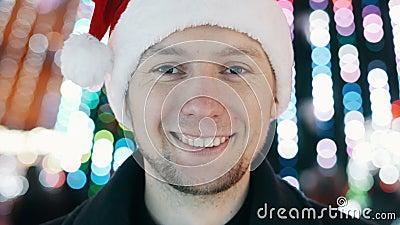 Młody wesoły mężczyzna portret z sylwestrowym uśmiechem i patrzeniem na kamerę, bokeh of the Christmas garland lights zdjęcie wideo