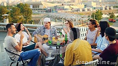 Młodzi ludzie mają zabawę na dachu bawić się gitarę, śpiew, gawędzenie i roześmianego obsiadanie, przy stołem outdoors joyce zdjęcie wideo