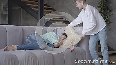 A m?e nova cai adormecido em casa O filho adolescente põe o descanso sob a cabeça da mulher e encontra-se então perto da mamã A m vídeos de arquivo