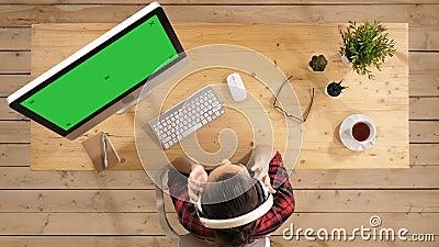 M?sica de escuta da mulher de neg?cios relaxado nos fones de ouvido na ruptura de trabalho Exposi??o verde do modelo da tela video estoque