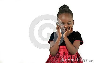 Mała amerykanin afrykańskiego pochodzenia dziewczyna używa telefon komórkowego