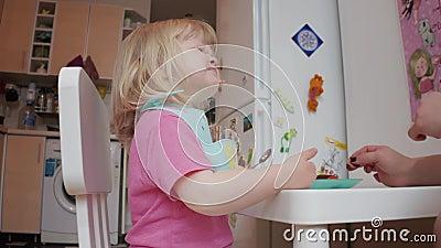 Mała, dwuletnia blond, niebieskooka dziewczynka jadająca obiad, 4K zastrzelona zbiory wideo