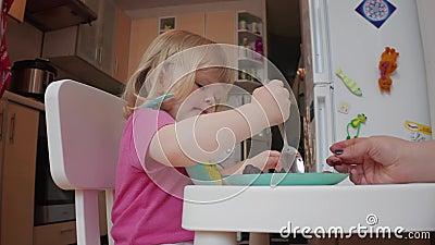 Mała, dwuletnia blond, niebieskooka dziewczynka jadająca obiad, 4K zastrzelona zbiory