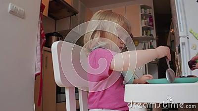 Mała, dwuletnia blond, niebieskooka dziewczynka jadająca obiad, 4K zastrzelona zdjęcie wideo