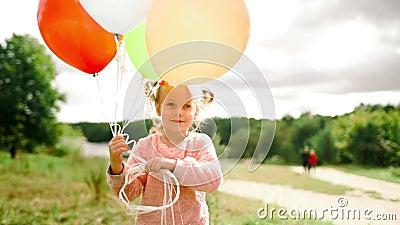 Mała dziewczynka z balonami w parku zdjęcie wideo