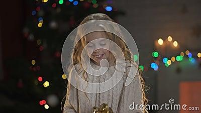 Małego blond dziewczyny mienia teraźniejsza poniższa choinka, magiczna zimy atmosfera zbiory