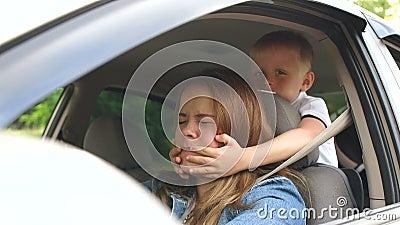 Mały chłopiec zamyka oczy matki prowadząc samochód Upośledzenie dzieci w samochodzie zdjęcie wideo
