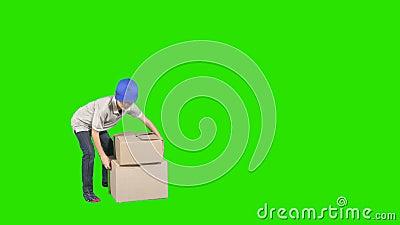 Mały deliveryman w nakrętce przynosi pudełka przy zielonym tłem zdjęcie wideo
