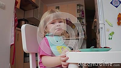Mały, dwuletni blond, niebieskooka dziewczyna grimaces podczas obiadu, 4K zastrzelony zdjęcie wideo