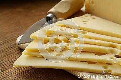 Maasdam cheese sliced on board