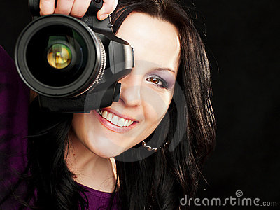 Macchina fotografica della holding della donna del fotografo sopra oscurità