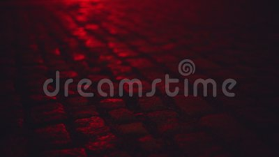 Machen Sie belichtet durch den Kopfstein des roten Lichtes nass, der Straße nachts pflastert stock footage